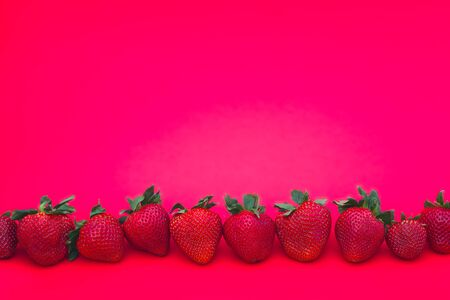 strawberries in a row on pink background Stock Photo