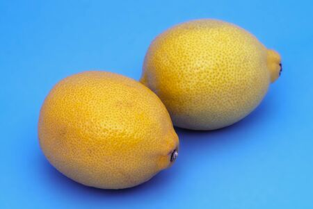 yellow lemons on blue background healthy fruits