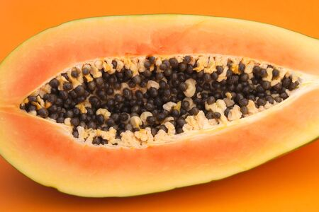 jumbo papaya on orange background cut in half tropical fruit with seeds