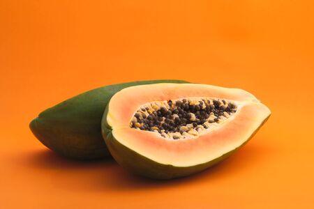 jumbo papaya on orange background sliced tropical fruit with seeds