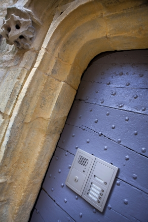 contradictory: Old door and intercom on a facade of a house in Sarlat, Dordogne, France Stock Photo
