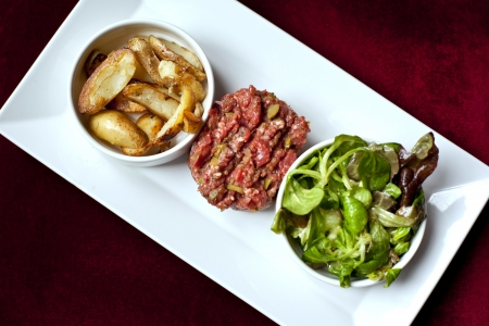 steak tartare: Steak tartare, french fries and salad on a plate Stock Photo