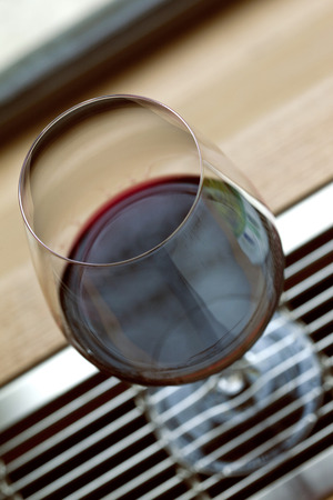 oenology: Glass of Bordeaux red wine on a table Stock Photo