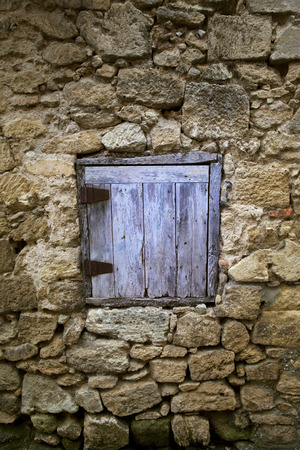 misery: Old wooden shutter of a stoned house