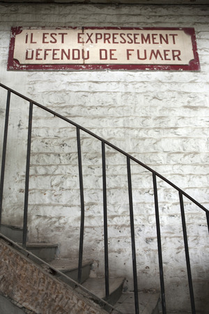 metal handrail: No smoking sign in an old French warehouse