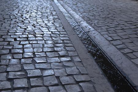 empedrado: Calle pavimentada y cuneta en la ciudad Foto de archivo