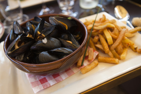 Mussels and French fries on a table in a French restaurant