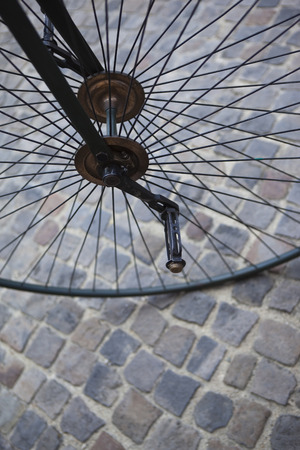 velocipede: Metal wheel of an old velocipede on a cobbled square Stock Photo
