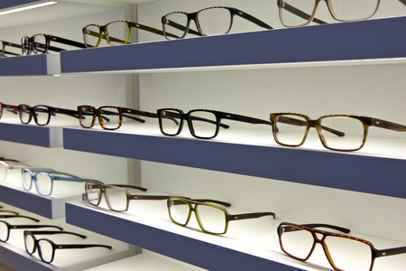 optician: Glasses on shelves in a optician shop Stock Photo