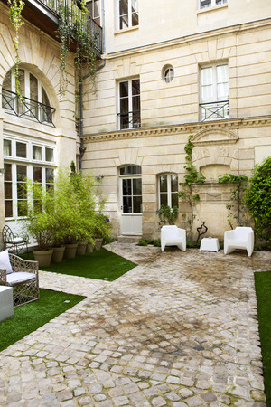 garden furniture: Plants and garden furniture in the courtyard of a French mansion