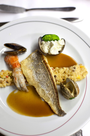 langoustine: Fish, cereals, langoustine and shells on a plate Stock Photo