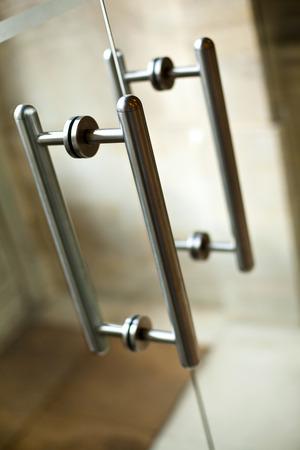 Stylish aluminum handles of a glass door Foto de archivo