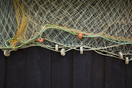 Fishing net on hanging on a wooden wall photo