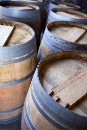 oenology: Close up of oak barrels in a French winery Stock Photo