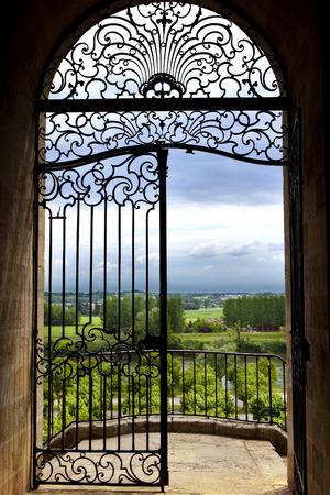 Smeedijzeren hek met uitzicht op het platteland in de buurt van Borderaux, Frankrijk