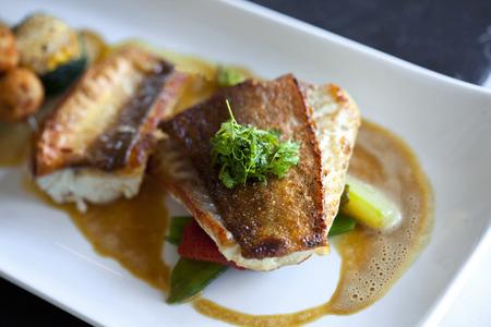 plato de pescado: Saint-Pierre pescado, verduras, setas y salsa en un plato Foto de archivo