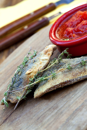 tomato puree: Breaded sardines and thyme, tomato puree in a bowl Stock Photo