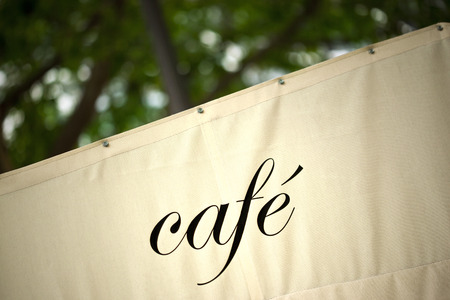 an awning: Canvas awning of a French bistro in a park Stock Photo