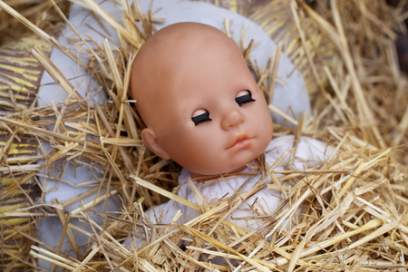 manger: Head doll and straw in a manger for Christmas