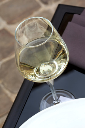 french cafe: White wine in glass, terrace of a French cafe Stock Photo