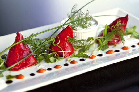 herbe: Peppers stuffed with cod, green salad and sauce on a plate Stock Photo