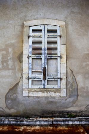 misery: Dead window and broken shutter of a slum