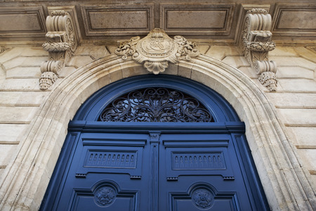 stoned: Wooden blue door on the stoned facade of a French mansion