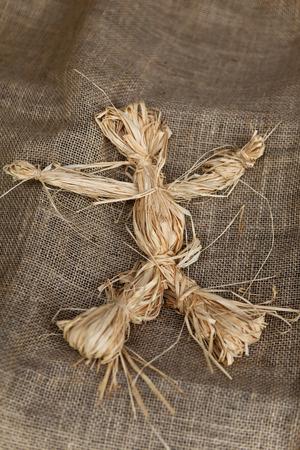 raffia: Close up of a raffia doll on a burlap fabric