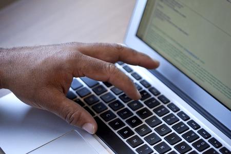 keywording: Man keywording on a computer at the office