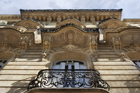 stoned: Windows and sculptures on the stoned facade of a French mansion in Bordeaux Stock Photo