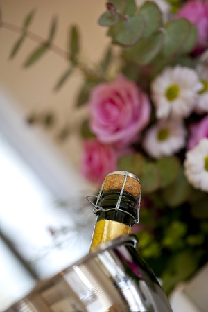 glower: Bottle of champagne in a bucket and bunch of flowers in a wine bar Stock Photo