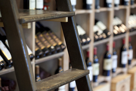 stool: Bottles and stool in a wine shop Stock Photo