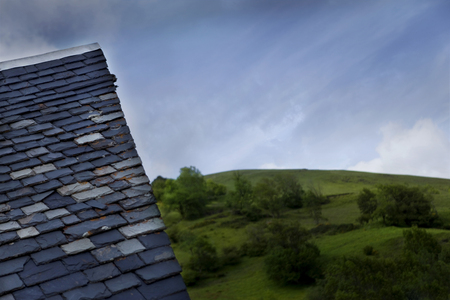 slate roof: Slate roof of an old chalet and green fields in Pyrenees, France