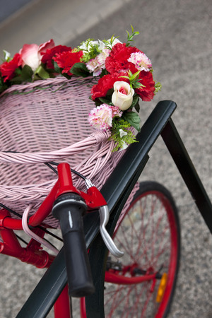 Flowers and wicker basket on a bike parked on the street Stock Photo