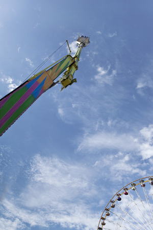 fairground: Ride and big wheel at a fairground in Summer Stock Photo