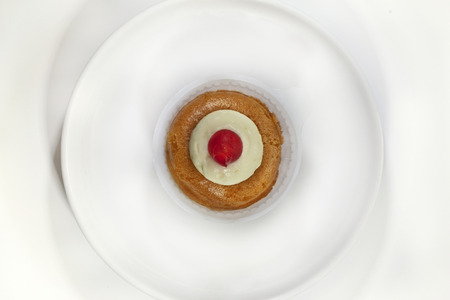 rum cake: French rum cake and cherry on a plate