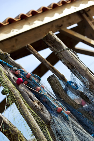 and the stakes: Fishing nets and buoys hanging on wooden stakes front of a fishermans hut