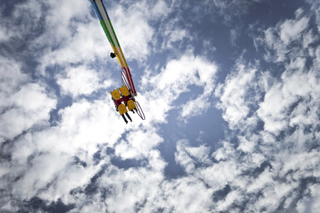 fairground: Teens on a ride at a fairground, blue sky on background Stock Photo