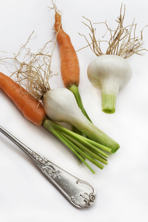 Carrots, onions and fork on a white table
