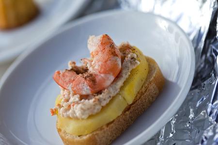 Garnalen, zeevruchtenmousse en plak van aardappel op een toost Stockfoto