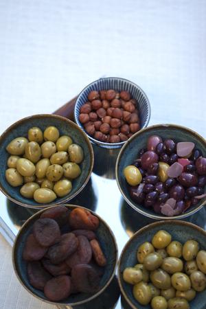 Olijven en hazelnoten en gedroogde vruchten op kommen Stockfoto