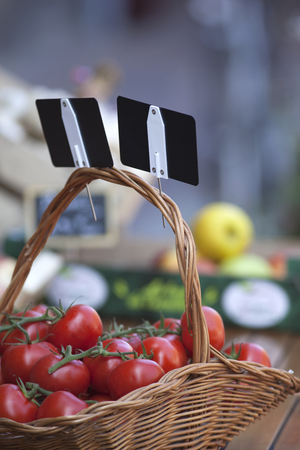 Tomatoes in a wicker basket on a market stall