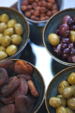 Olive and dried fruits in porcelain bowls