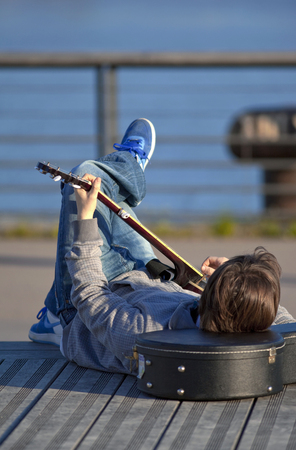 Playing guitar lying on a wooden terrace Stock Photo