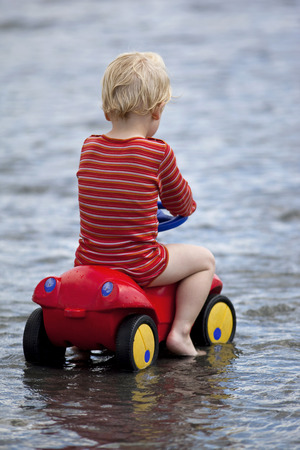 Young kid playing on a plastic miniature car