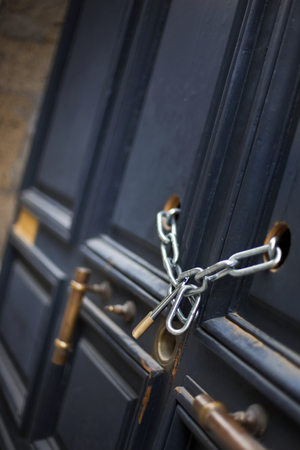 Chains and padlock on a wooden door