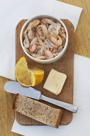 Shrimps butter and lemon on a wooden board