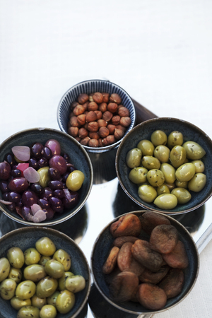 Hazelnuts olives and dried fruits in bowls Фото со стока