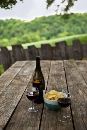 Tasting glass of red wine and chips on a terrace in the French countryside