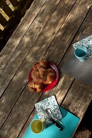 Croissants and coffee cups on a wooden table for a breakfast in the countryside